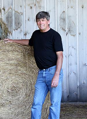 Landowner Barry Wright standing beside a hay bale